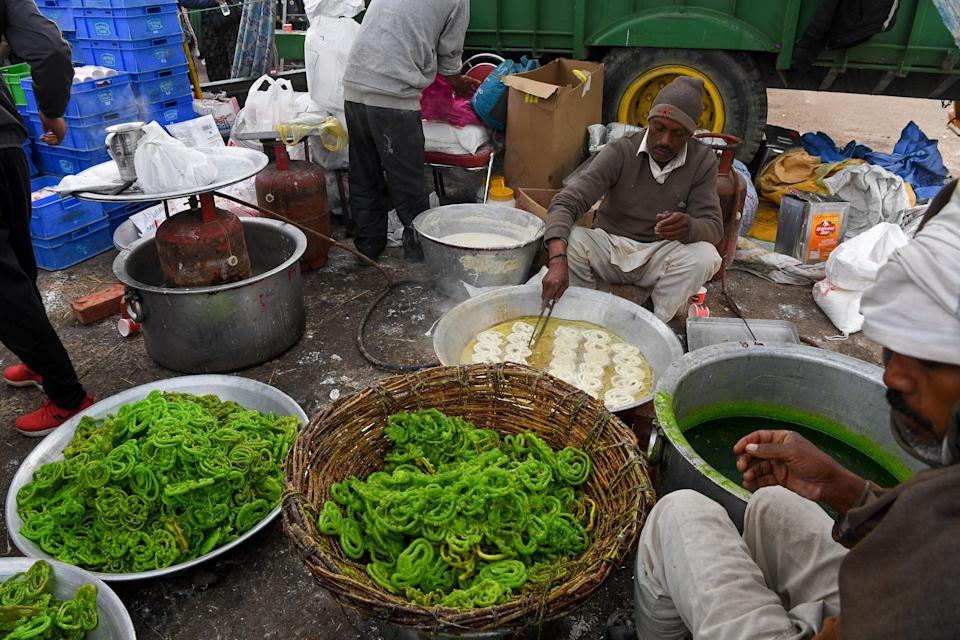Volunteers prepare 'Jalebi', a sweet dish for breakfast as farmers continue to demonstrate against the central government's recent agricultural reforms while blocking a highway at the Delhi-Haryana state border in Singhu on December 30, 2020. (Photo by Prakash SINGH / AFP) (Photo by PRAKASH SINGH/AFP via Getty Images)