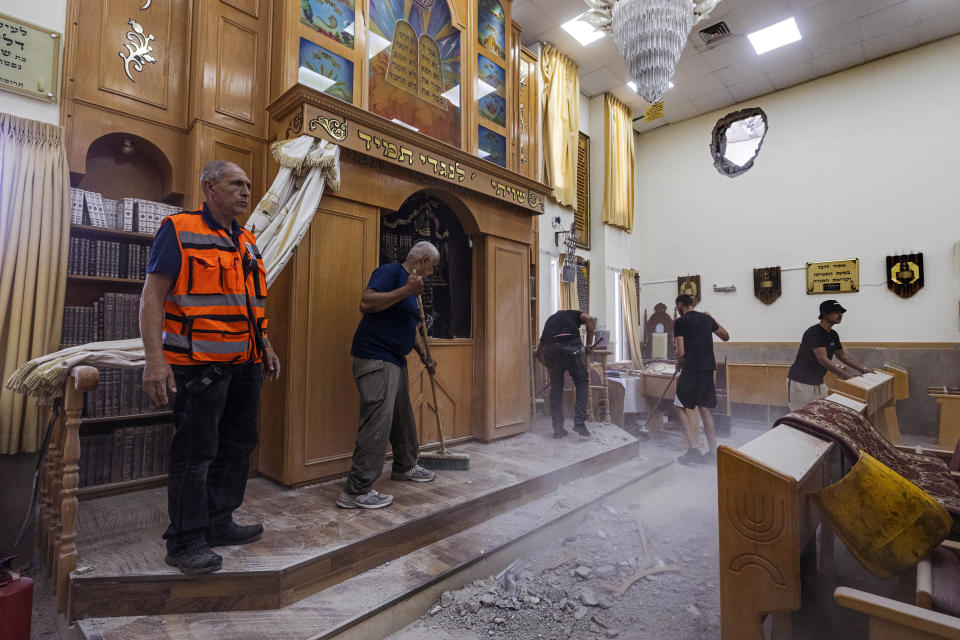 People clean a damaged synagogue after it was by a rocket fired from the Gaza Strip, In Ashkelon, Israel, Sunday, May 16, 2021. (AP Photo/Tsafrir Abayov)