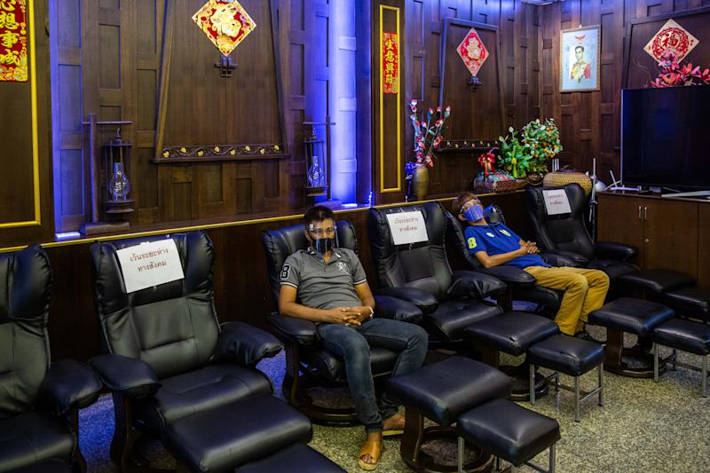 Massage parlor staff sit in socially distanced chairs on their first day of reopening after the COVID-19 pandemic restrictions were lifted on June 1, 2020 in Bangkok, Thailand. (Photo by Lauren DeCicca/Getty Images)