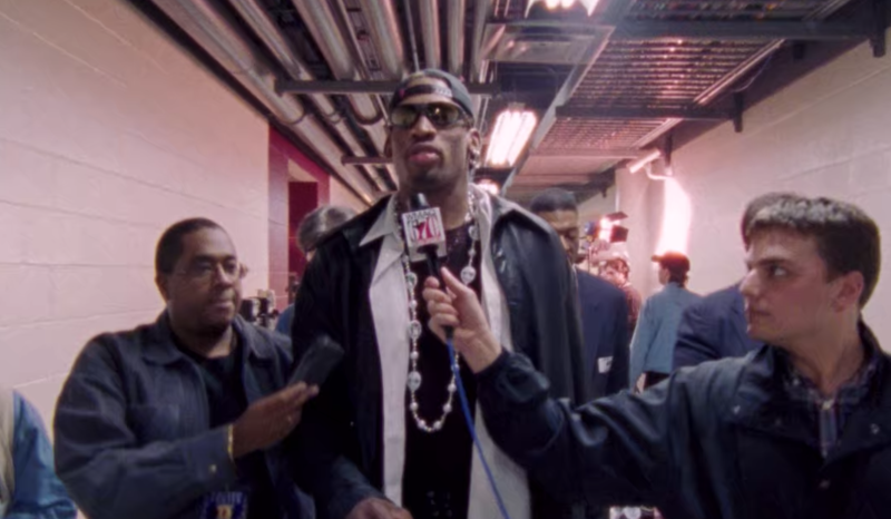 Dennis Rodman surrounded by reporters in Netflix's The Last Dance.