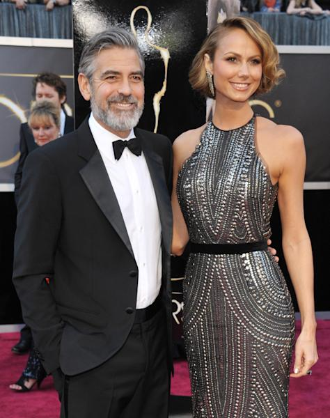 FILE - In this Feb. 24, 2013 file photo, actor George Clooney, left, and Stacy Keibler arrive at the Oscars at the Dolby Theatre in Los Angeles. Clooney, 52, Hollywood's most determined bachelor famous for a litany of fleeting loves, including Keibler, has taken himself off the romantic market and proposed to 36-year-old attorney, Amal Alamuddin. A spokesman for the Oscar-winning actor and producer did not respond to requests for comment Monday, April 28, 2014. (Photo by John Shearer/Invision/AP, file)