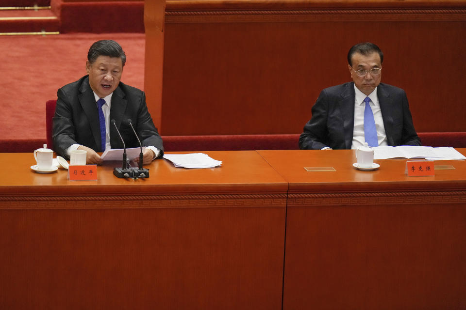 Chinese President Xi Jinping, left, delivers a speech next to his Premier Li Keqiang at an event commemorating the 110th anniversary of Xinhai Revolution at the Great Hall of the People in Beijing, Saturday, Oct. 9, 2021. (AP Photo/Andy Wong)
