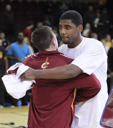 Cleveland Cavaliers' Kyrie Irving, right, hugs a fan during fan appreciation after an NBA basketball game between the Cavaliers and the Washington Wizards, Wednesday, April 25, 2012, in Cleveland. Washington won 96-85. (AP Photo/Tony Dejak)