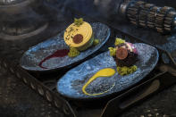 """The Oi-oi Puff (raspberry cream puff with passionfruit mousse) and Batuu-bon (raspberry cream puff with passion fruit mousse) can be found at Docking Bay 7 Food and Cargo. The names of these luscious desserts were <a href=""""https://www.yahoo.com/entertainment/star-wars-galaxy-edge-food-secrets-inside-disneyland-disney-world-galactic-menu-212455244.html"""" data-ylk=""""slk:revealed by Yahoo Entertainment in April;outcm:mb_qualified_link;_E:mb_qualified_link;ct:story;"""" class=""""link rapid-noclick-resp yahoo-link"""">revealed by Yahoo Entertainment in April</a>. (Photo: David Roark/Disney Parks)"""