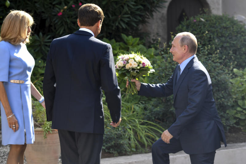 Russian President Vladimir Putin arrives with a bouquet of flowers as French President Emmanuel Macron, center, and his wife Brigitte look on at the fort of Bregancon in Bormes-les-Mimosas, southern France, Monday Aug. 19, 2019. French President Emmanuel Macron and Russian President Vladimir Putin are meeting to discuss the world's major crises, including Ukraine, Iran and Syria, and try to improve Moscow's relations with the European Union. (Gerard Julien, Pool via AP)