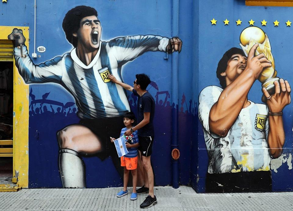 A man and his child pay tribute next to a mural depicting MaradonaAFP via Getty Images