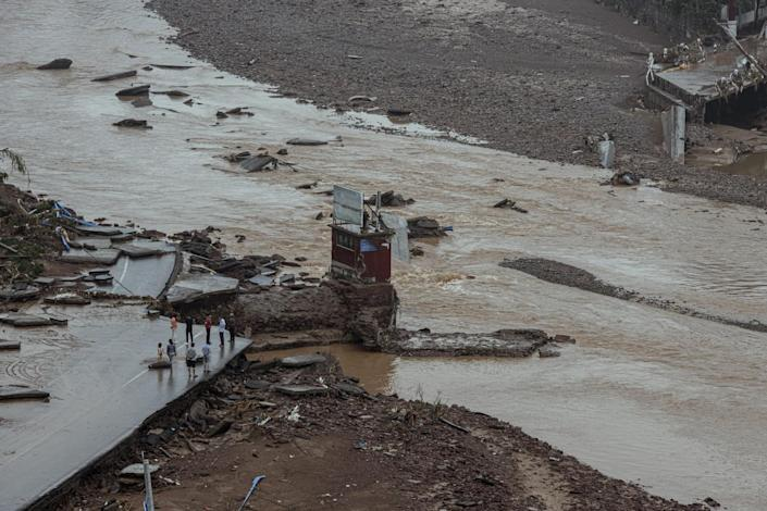 A view of people standing at the edge of a bridge, part of which has been washed away
