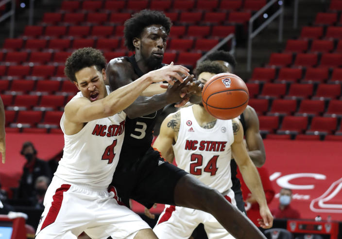 North Carolina State's Jericole Hellems (4) fights for a rebound with Miami's Nysier Brooks (3) during the second half of an NCAA college basketball game at PNC Arena in Raleigh, N.C., Saturday, Jan. 9, 2021. (Ethan Hyman/The News & Observer via AP)