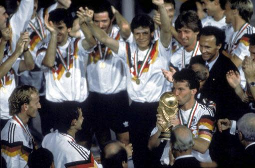 FILE - in this July 8, 1990 file photo, Germany's soccer captain Lothar Matthaus kisses the World Cup trophy after his team beat Argentina in the final 1-0 in the Olympic Stadium, in Rome, Italy. Coach Franz Beckenbauer, in dark jacket, stands behind Matthaus. The 21st World Cup begins on Thursday, June 14, 2018, when host Russia takes on Saudi Arabia. (AP Photo/Carlo Fumagalli, file)