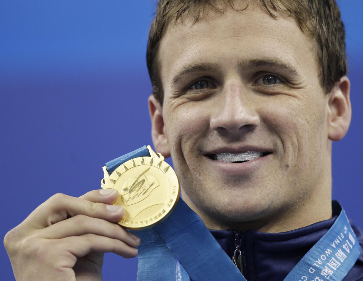 U.S. Ryan Lochte shows the gold medal he won in the men's 200m Backstroke final at the FINA Swimming World Championships in Shanghai, China, Friday, July 29, 2011. (AP Photo/Michael Sohn)