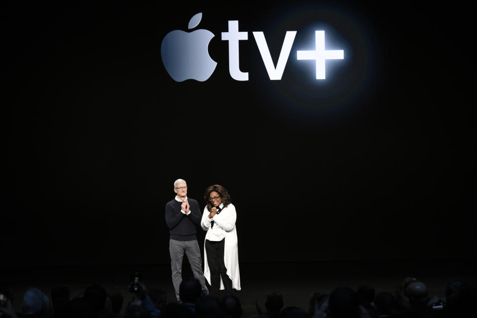 Apple Inc. CEO Tim Cook and Oprah Winfrey stand onstage during a company product launch event at the Steve Jobs Theater at Apple Park on March 25, 2019 in Cupertino, California. (Photo by Michael Short/Getty Images)