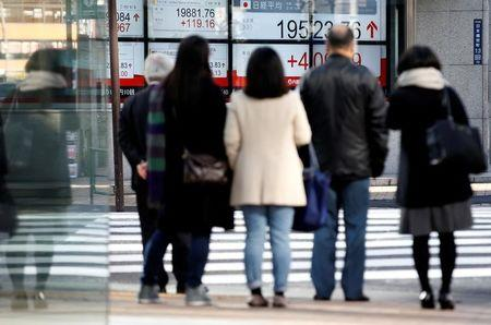People are seen in front of an electronic board showing stock prices outside a brokerage at a business district in Tokyo, Japan, January 4, 2017. Picture taken on January 4, 2017.  REUTERS/Kim Kyung-Hoon