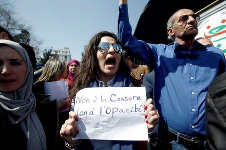 """Journalists working at state media carry banners and shout slogans during a protest in front of the state TV building to demand freedom to cover mass protests against President Abdelaziz Bouteflika, in Algiers, Algeria March 25, 2019. The banner reads, """"No to censorship, No to opacity"""".  REUTERS/Ramzi Boudina"""
