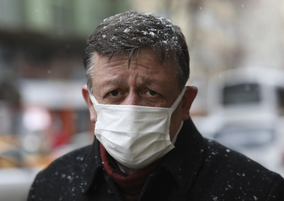 "A Turkish man wearing a mask to help protect against the spread of the coronavirus walks in Ankara, Turkey, Friday, March 26, 2021. Daily COVID-19 infections in Turkey surged above 26,000 on Friday, weeks after the government eased restrictions in dozens of provinces under a so-called ""controlled normalization"" program. (AP Photo/Burhan Ozbilici)"