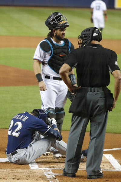 Milwaukee Brewers' Christian Yelich (22) sits on the ground after an injury while at bat as Miami Marlins catcher Jorge Alfaro, rear, and home plate umpire Kerwin Danley look on during the first inning of a baseball game, Tuesday, Sept. 10, 2019, in Miami. (AP Photo/Wilfredo Lee)