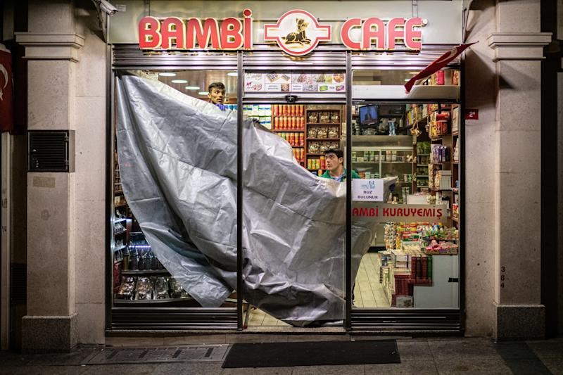 Most retail stores, cafes, restaurants and bars have closed in Istanbul, Turkey, as precautionary measures against the fast spreading coronavirus pandemic, also know as the Covid-19. Pictured above, workers at the iconic Bambi Cafe near Taksim Square hang a tarp over the entrance of the popular tourist fast food destination on March 25.