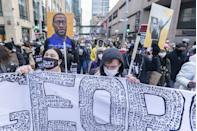 <p>Protesters march through the city streets on the day of closing arguments.</p>