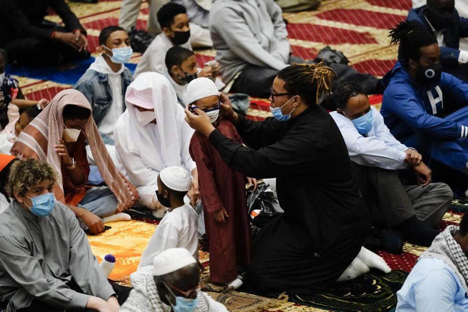 A worshipper helps a child with a mask before he and others perform an Eid al-Fitr prayer at the Masjidullah Mosque in Philadelphia, Thursday, May 13, 2021. Millions of Muslims across the world are marking the holiday of Eid al-Fitr, the end of the fasting month of Ramadan. (AP Photo/Matt Rourke)