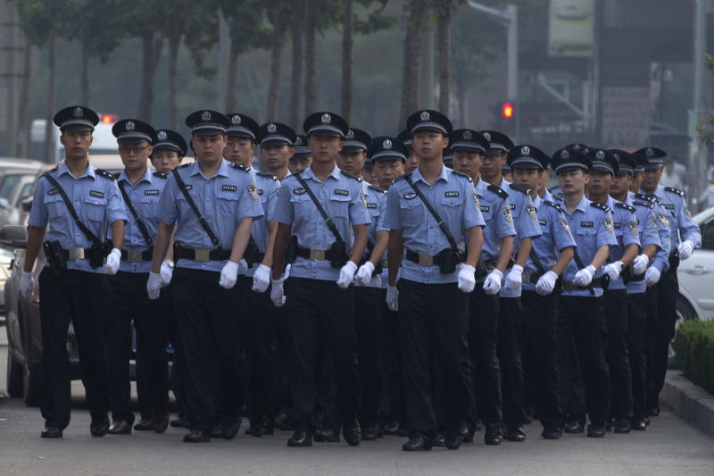 Chinese police officers prepare for the arrival of former politician Bo Xilai outside the Jinan Intermediate People's Court in Jinan, in eastern China's Shandong province on Thursday, Aug. 22, 2013. Former Chinese politician Bo Xilai will stand trial at the court on Thursday on charges of corruption and abuse of power. (AP Photo/Ng Han Guan)