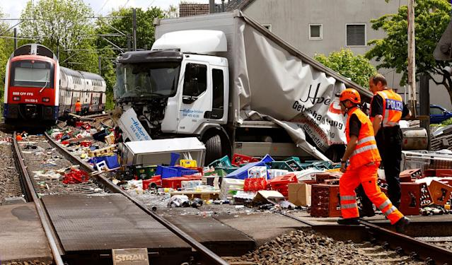 <p>A rescue worker and a Swiss police officer stand beside a truck transporting beverages which crashed with a suburban train on a railroad crossing in Horgen, Switzerland on May 12, 2017. (Photo: Arnd Wiegmann/Reuters) </p>
