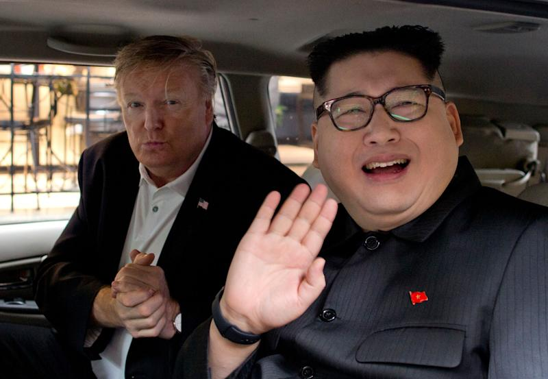Howard X, right, a Kim Jong Un impersonator, waves as Russel White, a President Donald Trump impersonator, gestures from a car outside La Paix hotel in Hanoi, Vietnam, on Monday.