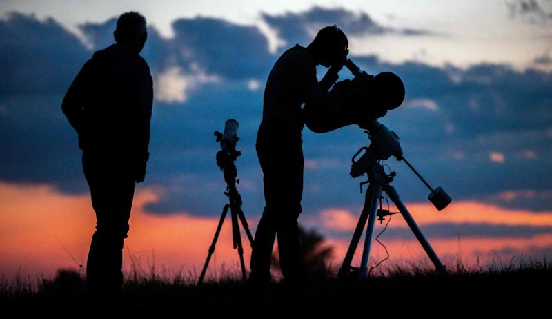People stand in front of their telescopes as they gather to wait for the partial lunar eclipse over Vienna (AFP/Getty Images)