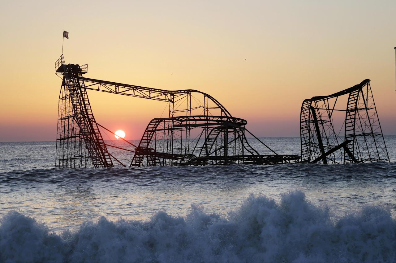 FILE - In a Feb. 25, 2013 file photo, the sun rises in Seaside Heights, N.J., behind the Jet Star Roller Coaster which has been sitting in the ocean after part of the Casino Pier was destroyed during Superstorm Sandy. Work is expected to start Tuesday afternoon, May 14, 2013 to remove the Jet Star coaster from the surf in Seaside Heights. (AP Photo/Mel Evans, File)