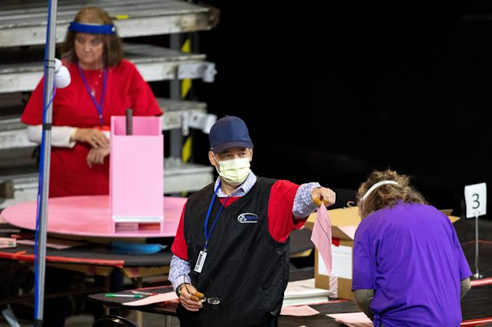 Contractors examine and recount ballots from the 2020 general election at Veterans Memorial Coliseum on May 1 in Phoenix. The Maricopa County ballot recount comes after two election audits found no evidence of widespread fraud.