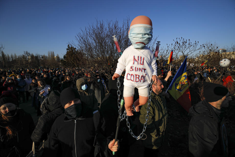 "Anti-vaccination protesters hold a doll with ""I don't want to be a lab rat"" written on it during a rally outside the parliament building in Bucharest, Romania, Sunday, March 7, 2021. Some thousands of anti-vaccination protestors from across Romania converged outside the parliament building protesting against government pandemic control measures as authorities announced new restrictions amid a rise of COVID-19 infections. (AP Photo/Vadim Ghirda)"