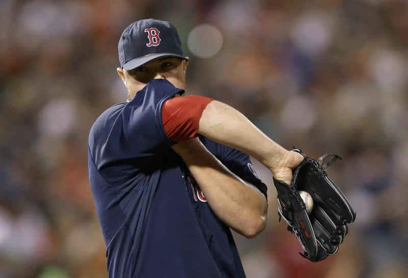 Boston Red Sox starting pitcher Jon Lester wipes sweat from his face between pitches during the second inning of a baseball game against the Baltimore Orioles, Saturday, Sept. 28, 2013, in Baltimore. (AP Photo/Patrick Semansky)