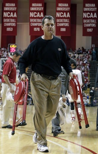 San Francisco 49ers NFL football head coach Jim Harbaugh carries off chairs for the Indiana players following a timeout in the first half of an NCAA college basketball game against North Carolina Central in Bloomington, Ind., Wednesday, Feb. 22, 2012. Harbaugh is the brother-in-law of Indiana head coach Tom Crean. (AP Photo/Michael Conroy)