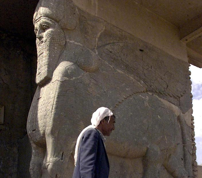 File photo of an Iraqi standing next to an ancient statue of a winged bull with a human face, an indication of strength in the Assyrian civilization, at the archaeological site of Nimrud, south of Mosul in northern Iraq (AFP Photo/)