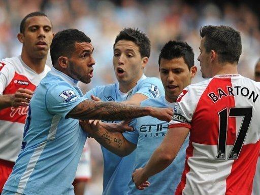 Queens Park Rangers' English midfielder Joey Barton (R) clashes with Manchester City's Argentinian striker Carlos Tevez (2nd L) during the match in Manchester. City were crowned Premier League champions after an incredible fightback which saw them score twice in injury time to beat QPR 3-2