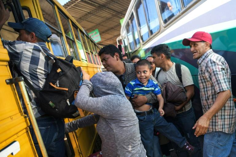 Salvadoran migrants board a bus, beginning their journeys in a caravan headed for the United States