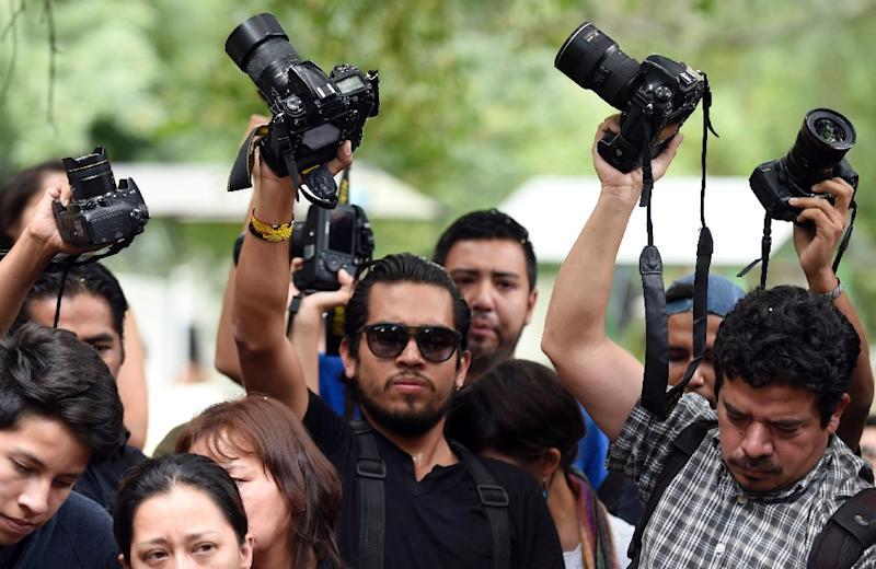 Colleagues and friends of murdered Mexican photographer Ruben Espinosa raise their cameras in salute over his coffin during his burial at the Dolores cemetery in Mexico City, on August 3, 2015 (AFP Photo/Alfredo Estrella)