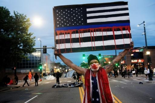 A demonstrator holds up a sign during a protest in Denver, Colorado over the death of George Floyd in police custody