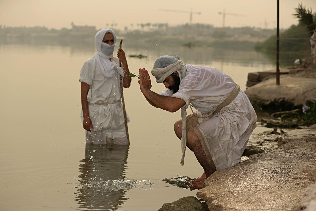 In this Sunday, Oct. 14, 2018 photo, followers of the ancient Mandaean religious sect perform their rituals along a strip of embankment on the Tigris River reserved for them, in Baghdad, Iraq. Mandaeanism follows the teachings of John the Baptist, a saint in both the Christian and Islamic traditions, and their rituals revolve around water. Iraq's soaring water pollution is threatening the religious rites of the tight-knit community, already devastated by 15 years of war. (AP Photo/Hadi Mizban)