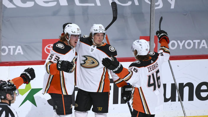 Anaheim Ducks left wing Max Comtois, center Rickard Rakell and center Trevor Zegras, from left, celebrate after Comtois scored the tying goal late in the third period of an NHL hockey game against the Minnesota Wild on Saturday, May 8, 2021, in St. Paul, Minn. The Wild won 4-3 in overtime. (AP Photo/Craig Lassig)