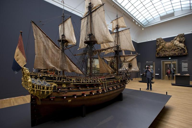 A photographer takes pictures of a 1698 model of the late 17th century Dutch warship William Rex during a press preview of the renovated Rijkmuseum in Amsterdam, Thursday April 4, 2013. The Rijksmusuem, home of Rembrandt's Night Watch and other national treasures, is preparing to reopen its doors on April 13 2013 after a decade-long renovation. (AP Photo/Peter Dejong)