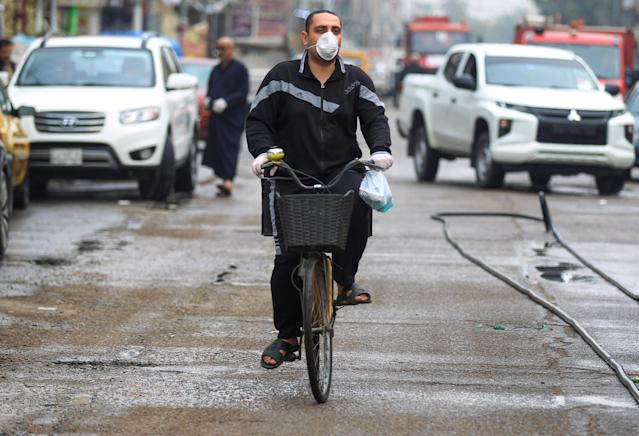 An Iraqi man, wearing a protective mask, rides a bicycle down street in the capital Baghdad on March 16, 2020 amidst efforts against the spread of COVID-19 coronavirus disease. (Photo by AHMAD AL-RUBAYE / AFP) (Photo by AHMAD AL-RUBAYE/AFP via Getty Images)