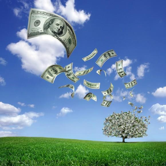 Wind blowing dollar bills from money tree against green grass and a clear blue sky.