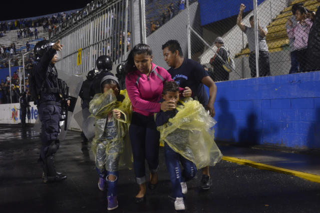 A family enters the perimeter of the soccer field to run away from tear gas that was fired by police to break up deadly fights, before the start of a game between the Motagua and Olimpia soccer teams at the national stadium in Tegucigalpa, Honduras, late Saturday, Aug. 17, 2019. The fight between fans of rival soccer teams outside the stadium left three people dead and led to the suspension of the game. (Victor Colindres/La Tribunal via AP)