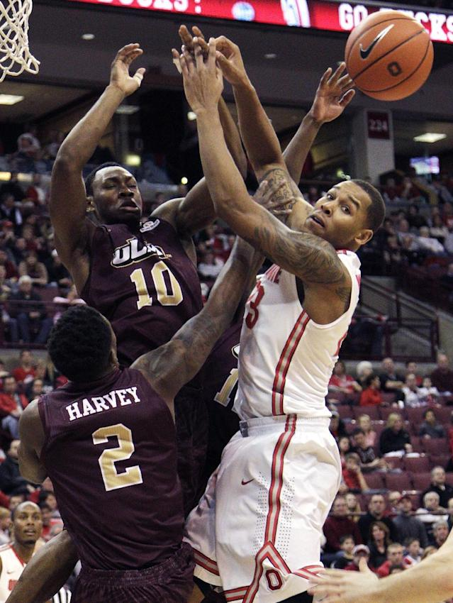 Ohio State's Amir Williams, right, tries to grab a rebound from Louisiana-Monroe's DeMondre Harvey, left, and Amos Olatayo during the first half of an NCAA college basketball game, Friday, Dec. 27, 2013, in Columbus, Ohio. (AP Photo/Jay LaPrete)