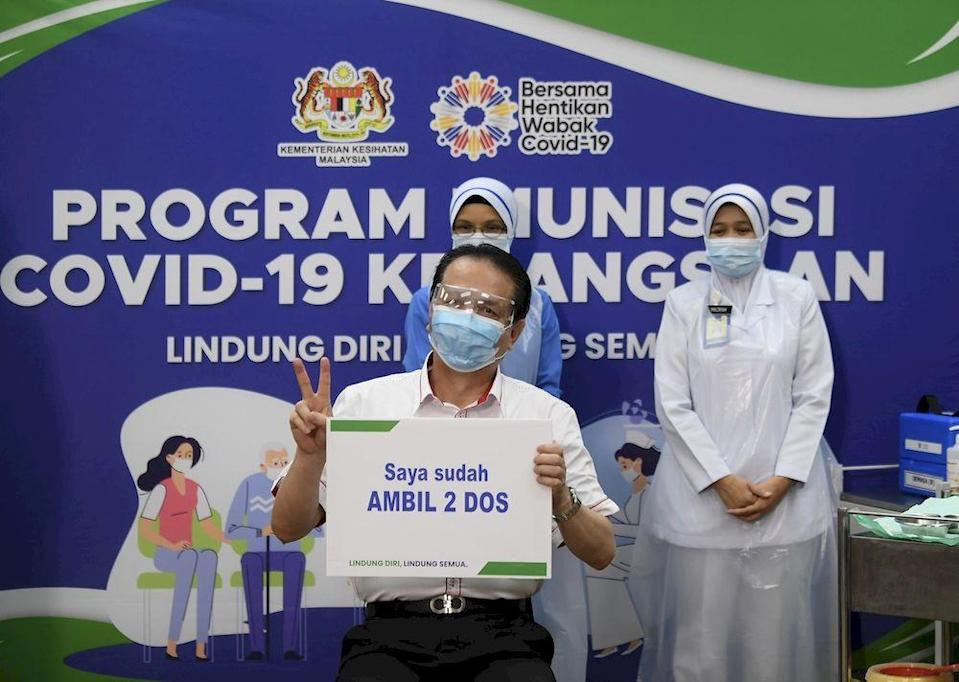 Director-General of Health Tan Sri Dr Noor Hisham Abdullah showing a placard 'I have TAKEN 2 DOS' after receiving the second injection of Pfizer-BioNTech Covid-19 vaccine from Chief Nurse Lina Ibrahim at the Putrajaya Precinct 18 Health Clinic, Putrajaya, March 17, 2021. — Bernama pic
