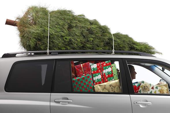 A woman driving a car filled with Christmas presents and a Christmas tree on top..To see more holiday images click on the link b
