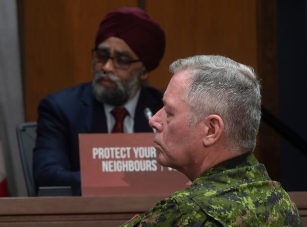 Chief of Defence Staff Jonathan Vance and Minister of National Defence Harjit Sajjan listen to a question during a news conference in Ottawa on March 30, 2020.