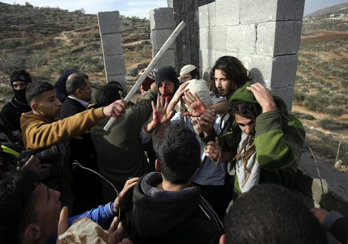 """Palestinians hit Israeli settlers while others try to stop them before a group of settlers were detained by Palestinian villagers in a building under construction near the West Bank village of Qusra, southeast of the city of Nablus, Tuesday, Jan. 7, 2014. Palestinians held more than a dozen Israeli settlers for about two hours Tuesday in retaliation for the latest in a string of settler attacks on villages in the area, witnesses said. The military said the chain of events apparently began after Israeli authorities removed an illegally built structure in Esh Kodesh, a rogue Israeli settlement in the area. In recent years, militant settlers have often responded to any attempts by the Israeli military to remove parts of dozens of rogue settlements, or outposts, by attacking Palestinians and their property. The tactic, begun in 2008, is known as """"price tag."""" (AP Photo/Nasser Ishtayeh)"""