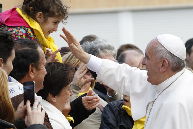 """Pope Francis greets faithful as he arrives at the Don Gnocchi Foundation Center to celebrate the rite of the washing of the feet, in Rome, Thursday, April 17, 2014. Pope Francis has washed the feet of 12 elderly and disabled people — women and non-Catholics among them — in a pre-Easter ritual designed to show his willingness to serve like a """"slave."""" Francis' decision in 2013 to perform the Holy Thursday ritual on women and Muslim inmates at a juvenile detention center just two weeks after his election helped define his rule-breaking papacy. It riled traditionalist Catholics, who pointed to the Vatican's own regulations that the ritual be performed only on men since Jesus' 12 apostles were men. The 2014 edition brought Francis to a center for the elderly and disabled Thursday. Francis kneeled down, washed, dried and kissed the feet of a dozen people, some in wheelchairs. He said the ritual is a gesture of """"a slave's service."""" (AP Photo/Riccardo De Luca)"""