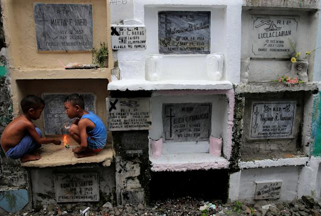 <p>Children play in front of the apartment tombs during the observance of All Saints' Day at Navotas public cemetery in Metro Manila, Philippines, Nov. 1, 2017. (Photo: Romeo Ranoco/Reuters) </p>