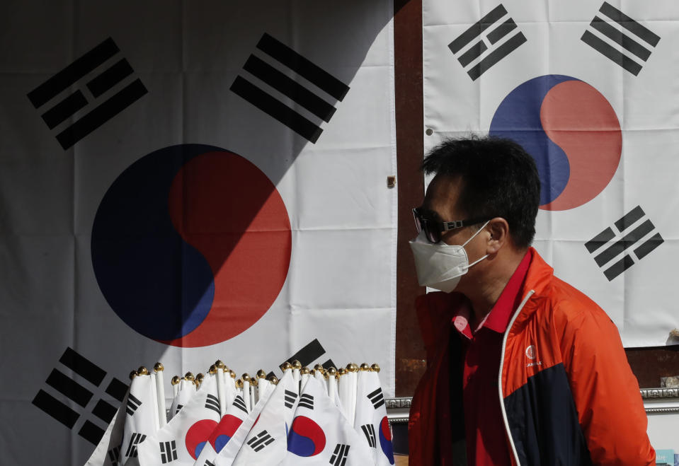 "A man wearing a face mask walks near national flags displayed at a souvenir shop at the Imjingak Pavilion in Paju, South Korea, Sunday, Oct. 11, 2020. North Korean leader Kim Jong Un warned that his country would ""fully mobilize"" its nuclear force if threatened as he took center stage at a military parade that unveiled what appeared to be a new intercontinental ballistic missile and other weapons Saturday. (AP Photo/Lee Jin-man)"